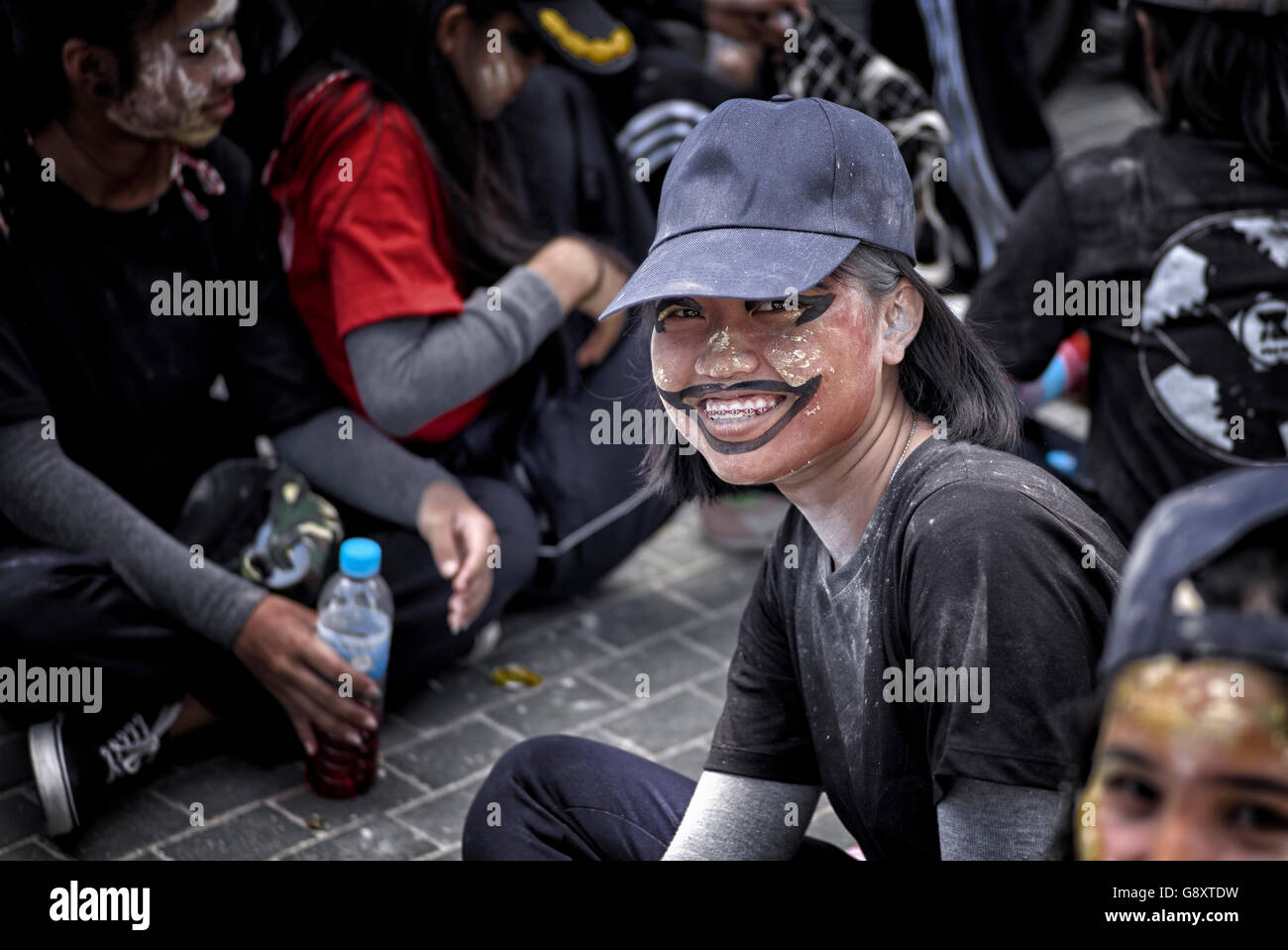 Thai teenagers staging a street mocking protest against excessive vanity by applying farcical face make up. Thailand - Stock Image