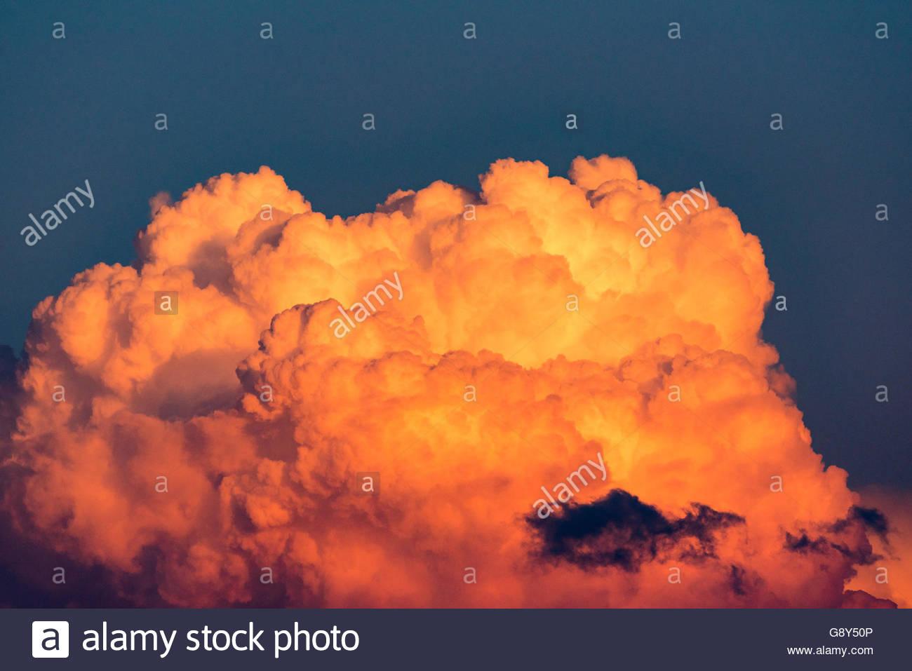 Colorful orange cloud cumulonimbus during sunset or dusk. - Stock Image