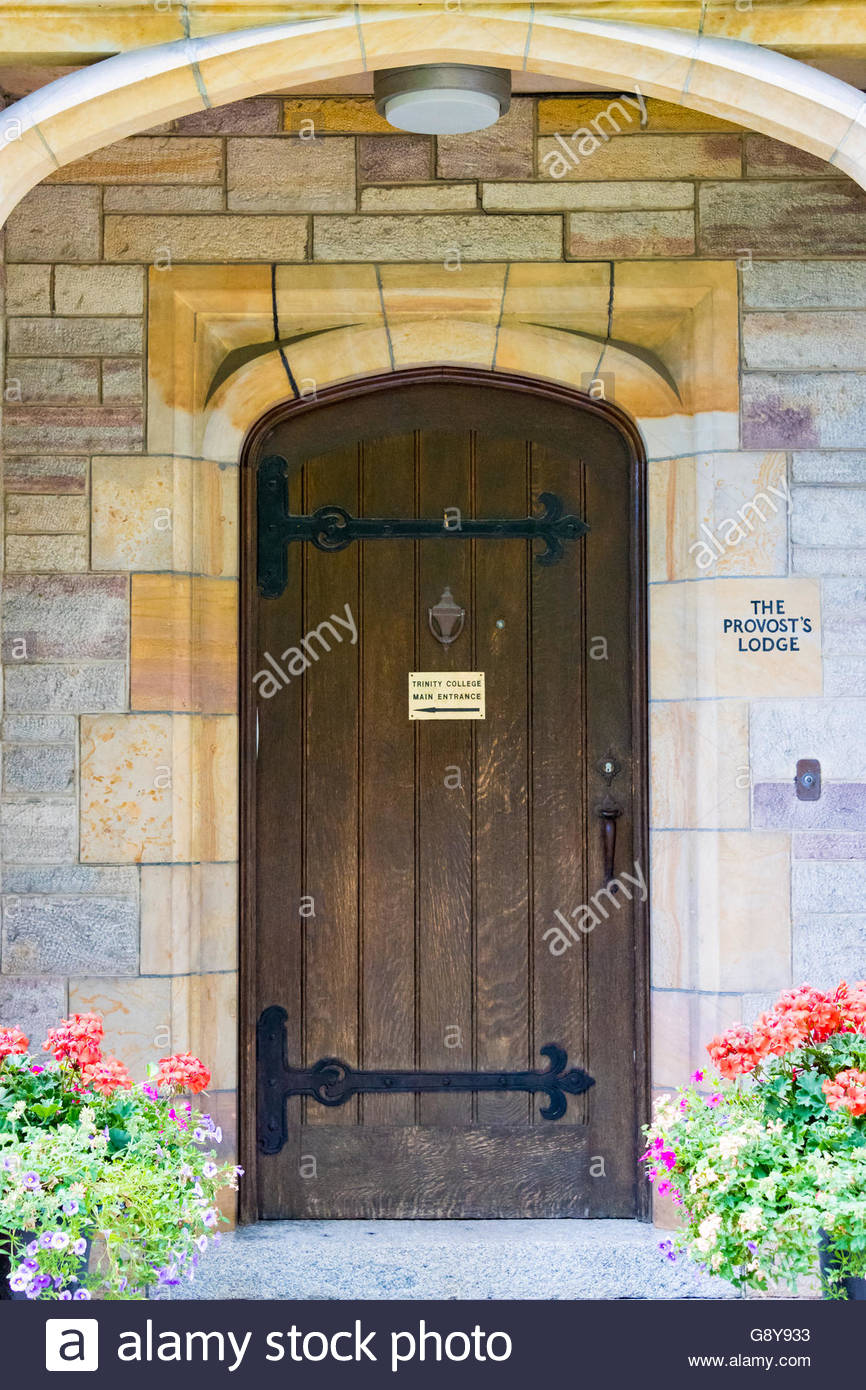 U of T or University of Toronto: Trinity College. Beautiful vintage wooden door with flowers at its side. The landmark - Stock Image
