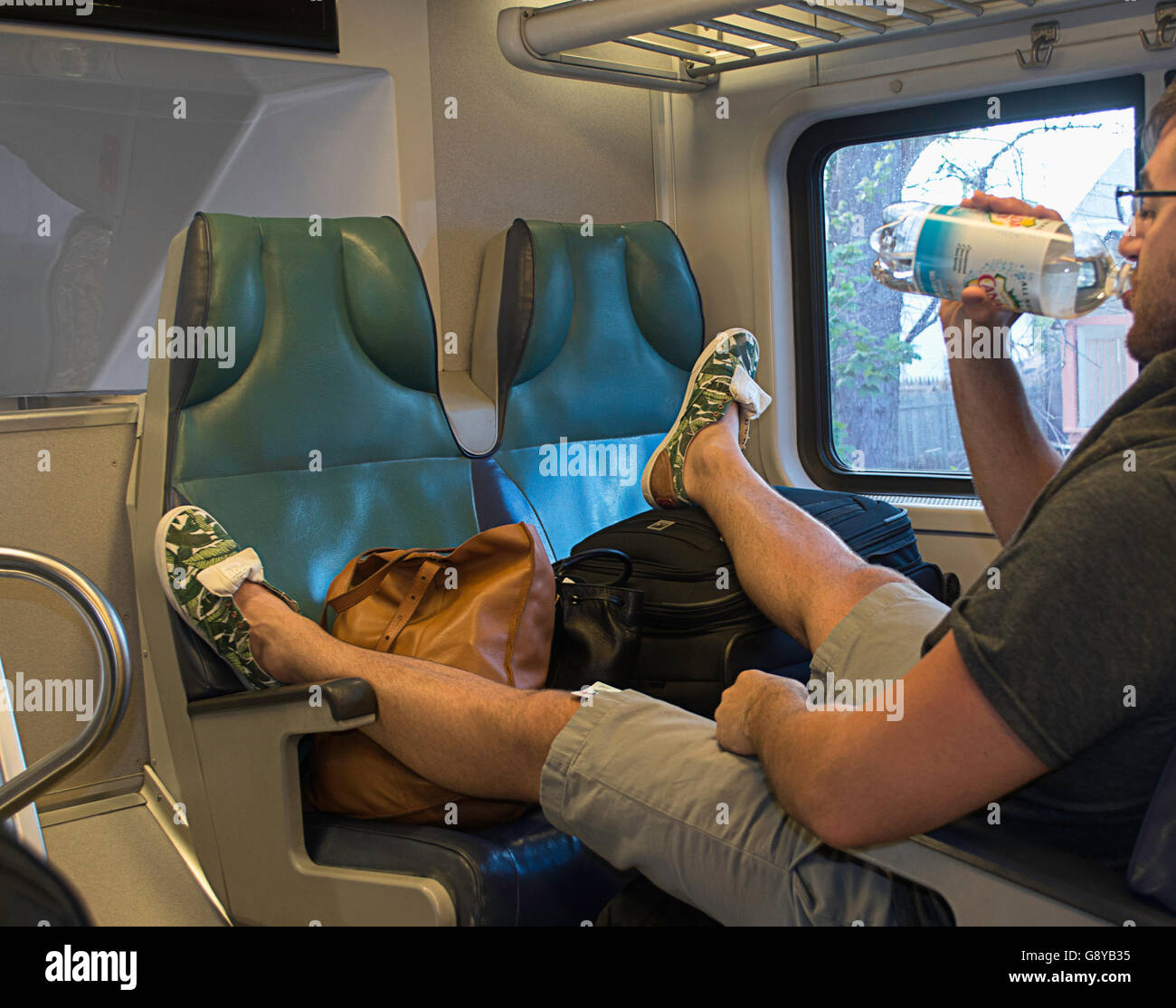 A rude man taking up too many seats on a train. - Stock Image