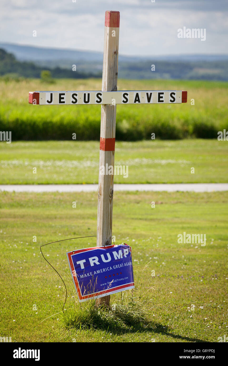 """New York State, USA, June 29, 2016: A rural evangelical voter places a Trump sign on a """"Jesus Saves"""" crucifix in Stock Photo"""