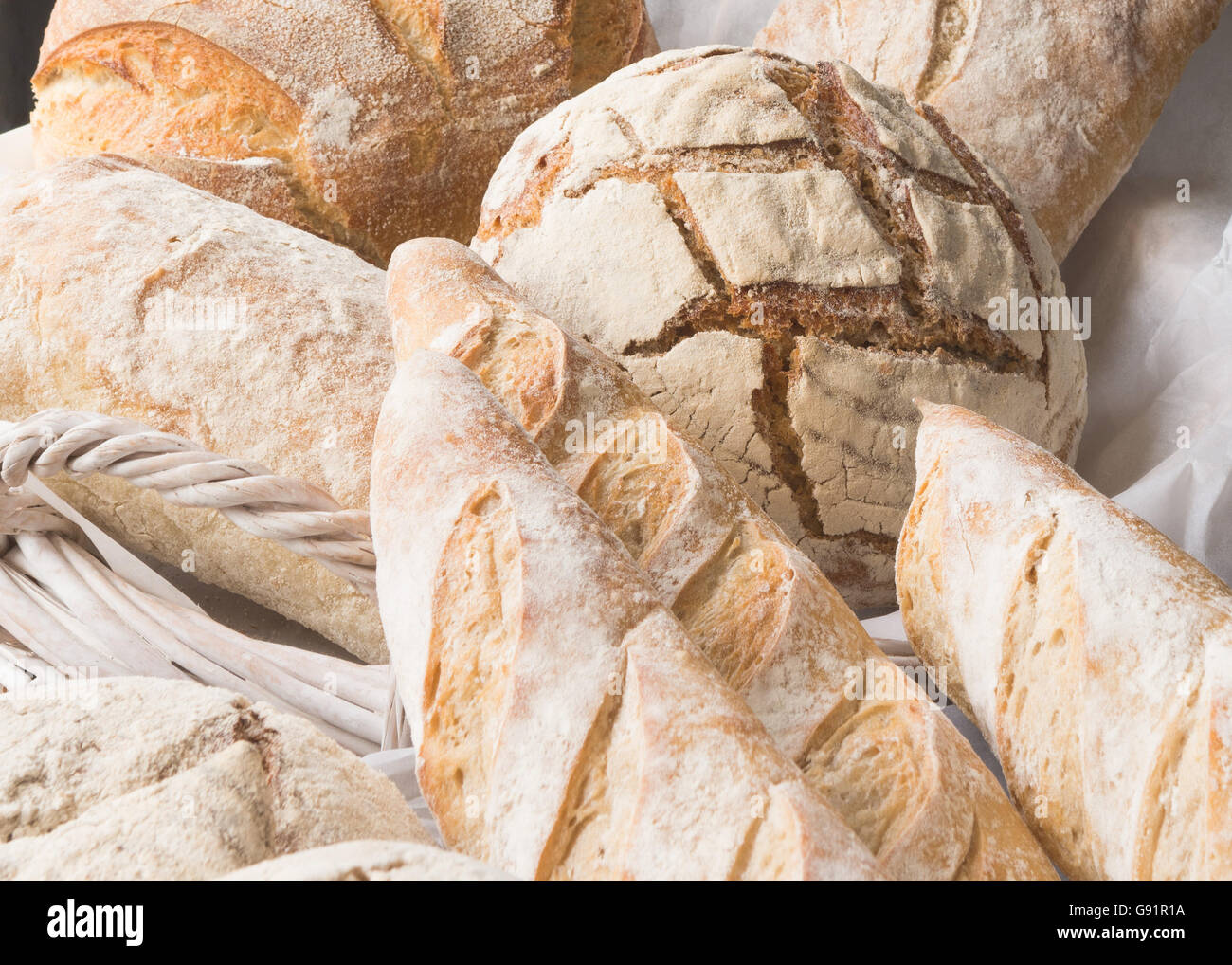 freshly baked artisan loaves of bread in white wicker basket - close up - Stock Image