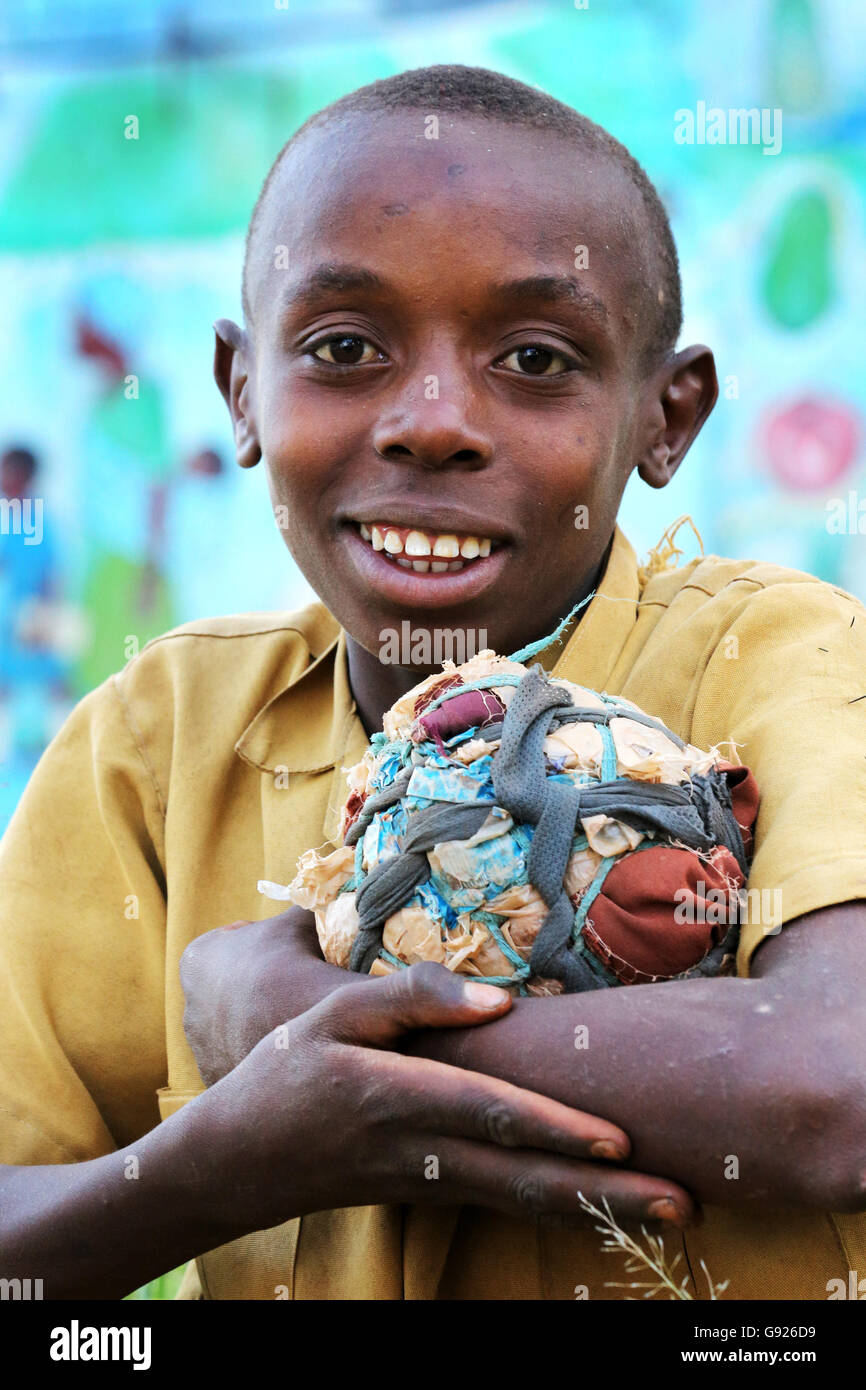 Young boy (12 years) with his self-made football made of fabric scraps and plastic bags in a village near Ruhengeri, - Stock Image