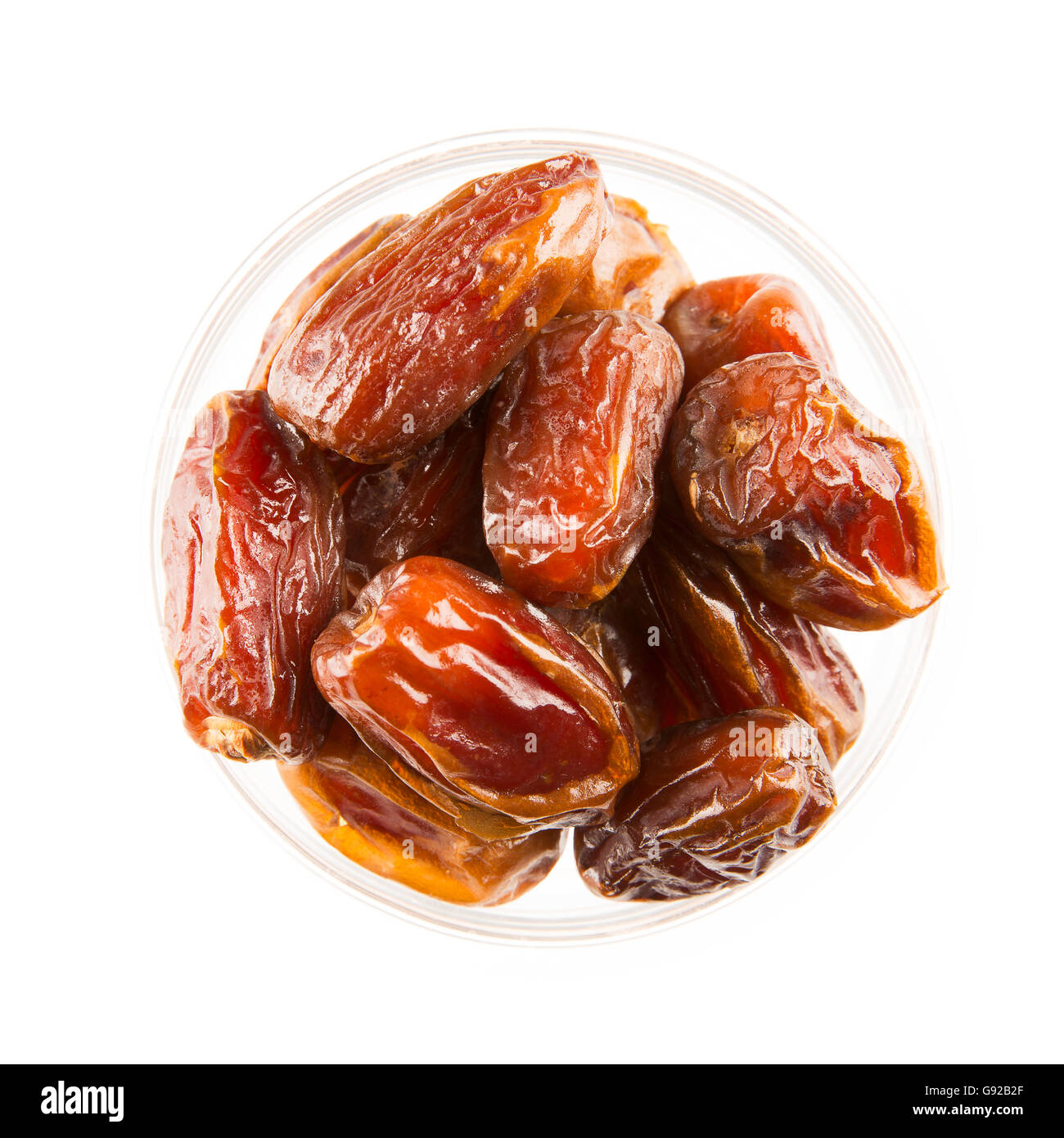 Dried dates in bowl, isolated on white and viewed from above. - Stock Image