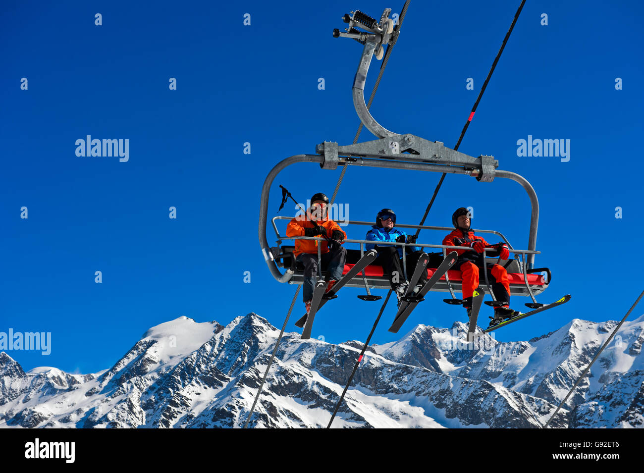 Skiers on a chair lift in the skiing area Les Contamines-Montjoie,  Mont Blanc massif behind, Haute-Savoie, France - Stock Image