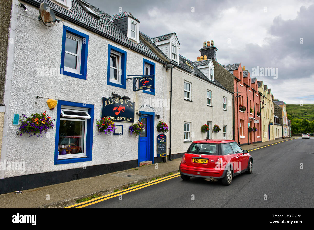 Red Mini car passing by the Harbour View Seafood Restaurant, Portree, Isle of Skye, Scotland, Great Britain - Stock Image