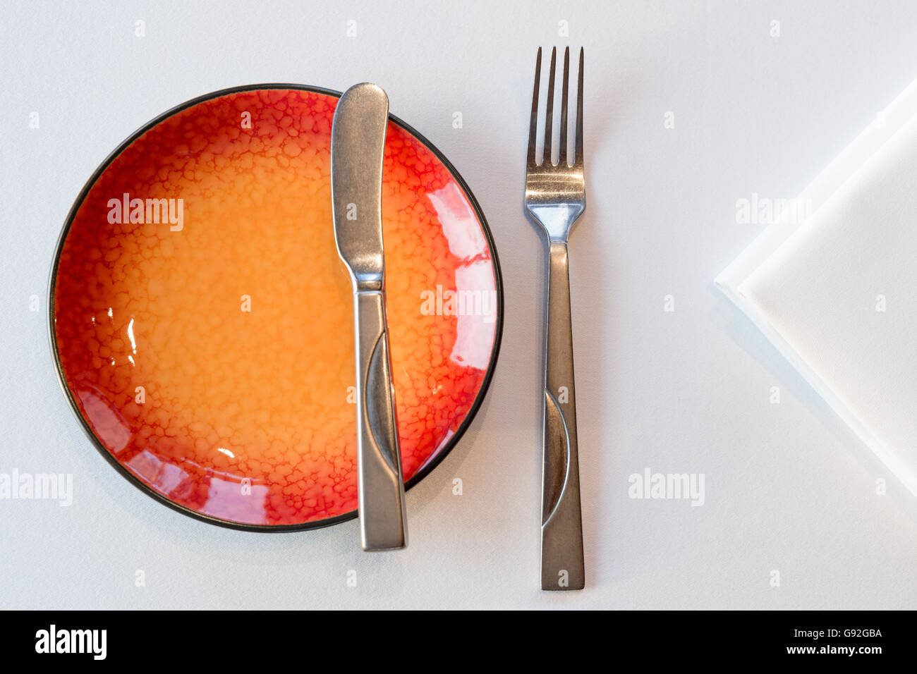Starter meal setup with red hot plate and white napkin decoration. Selective focus. & Starter meal setup with red hot plate and white napkin decoration ...