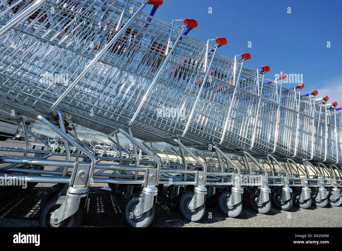 Shopping carts in a stack against a clear blue sky - Stock Image