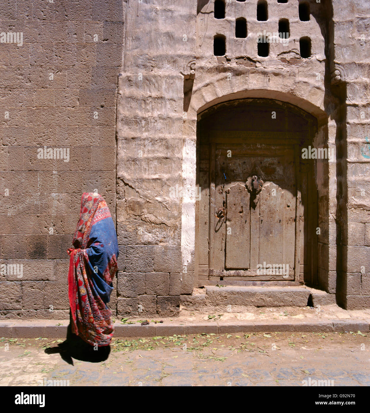 A veiled Muslim woman walks on a Sana'a street, Yemen. At background typical Yemen houses. - Stock Image