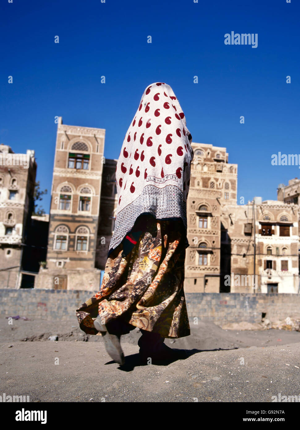 Sana'a, Yemen-February 12, 2012: A veiled Muslim woman walks on a Sana'a street, Yemen. At background typical - Stock Image
