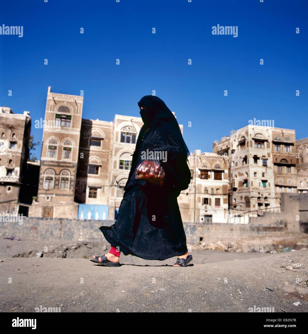 Veiled Muslim woman walks on  Sana'a street, Yemen. At background typical Yemen houses. Stock Photo