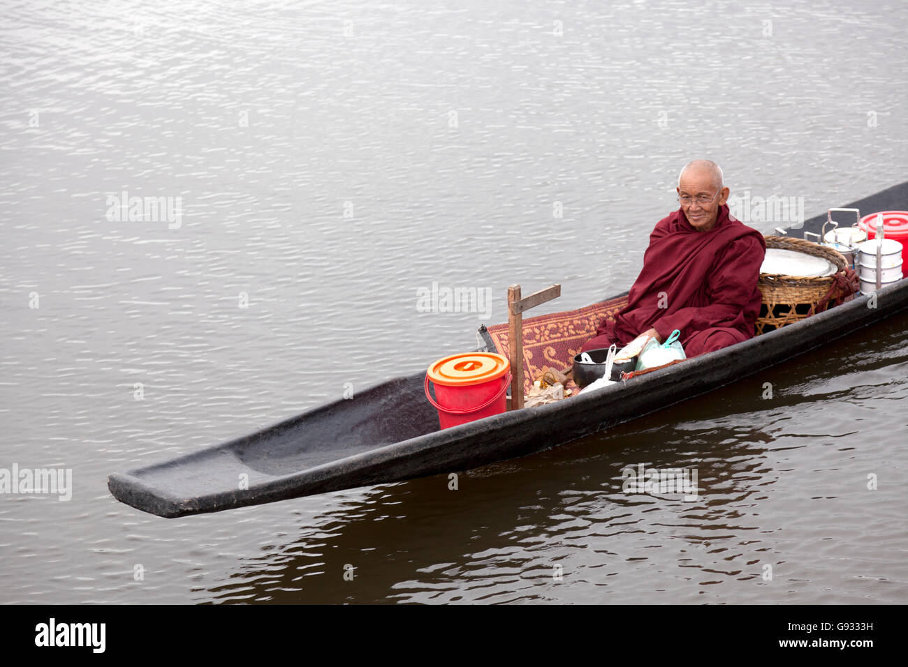 At the Maing Thauk lake side village, a monk coming back monastery by pirogue after his Alms Round (Inle Lake - - Stock Image
