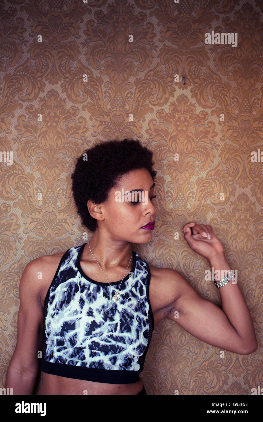 Beauty in dereliction : Fashion photography of a young afro-caribbean woman girl alone in an ornately  wall-papered - Stock Image