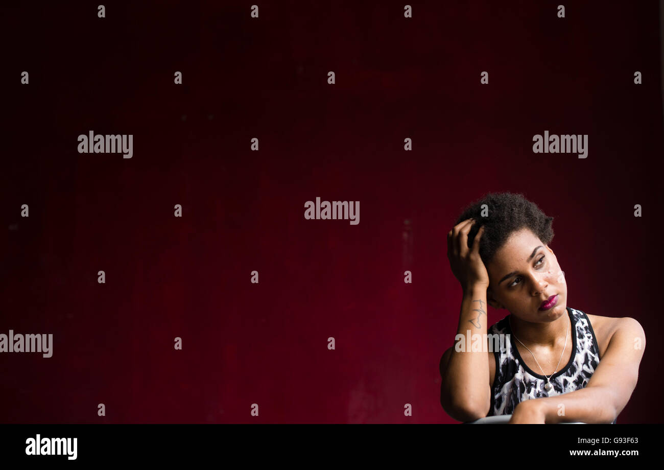 Beauty in dereliction : Fashion photography of a young afro-caribbean woman girl alone in a  red walled room  wearing - Stock Image