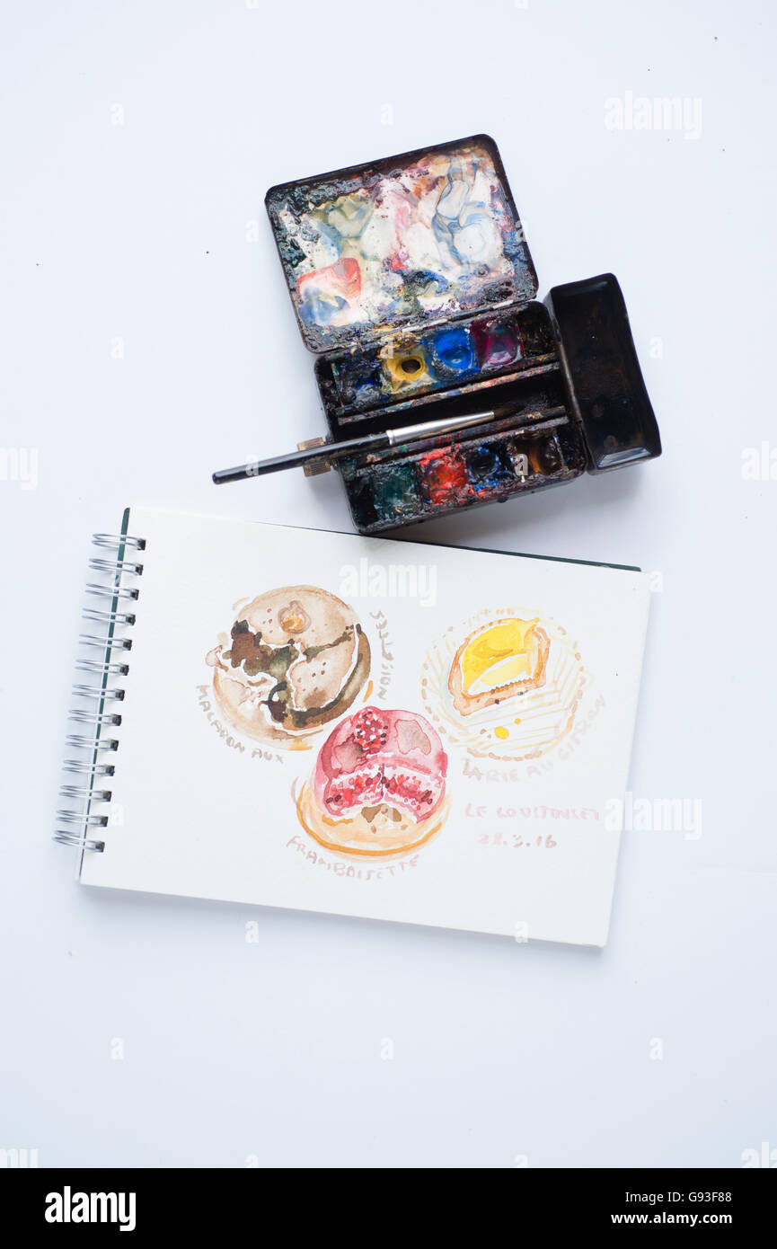 A small  well used watercolour artist's travel box of paints and sketch pad with little paintings of items of - Stock Image