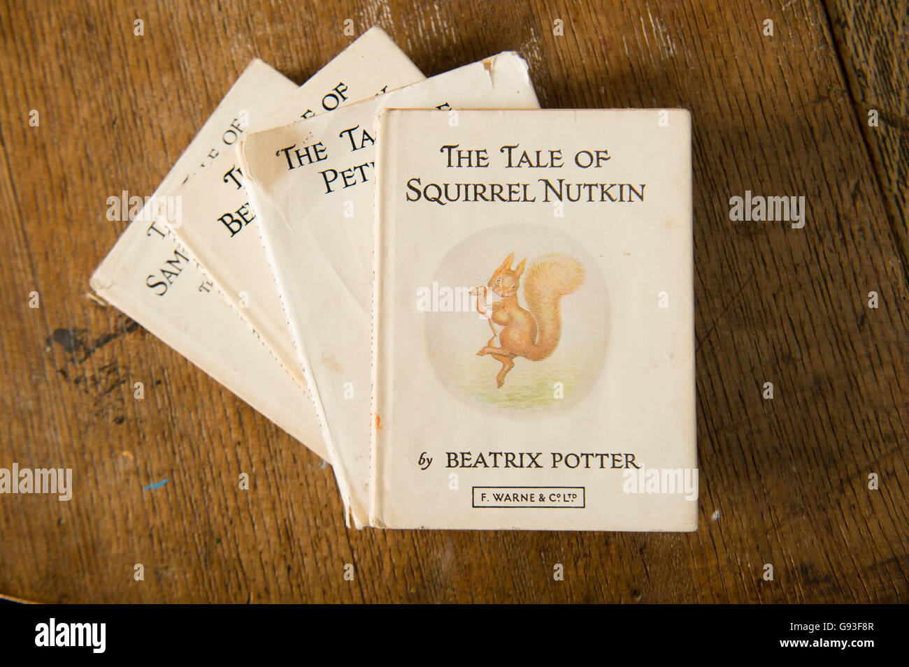 Classic English language children's literature: The Tale of Squirrel Nutkin on top of a stack of other books - Stock Image