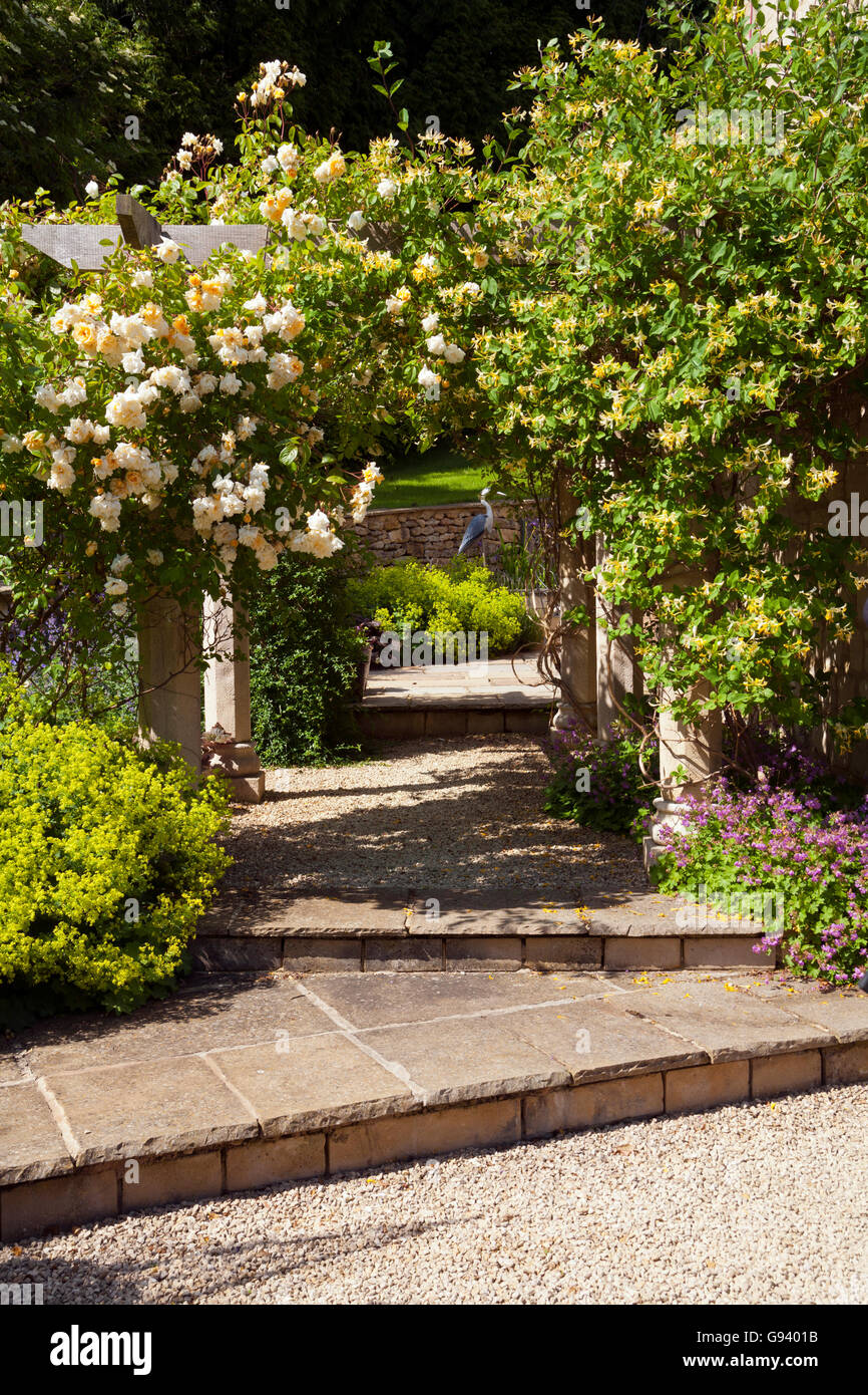 UK. A garden arch with roses and honeysuckle and patio beyond Stock ...