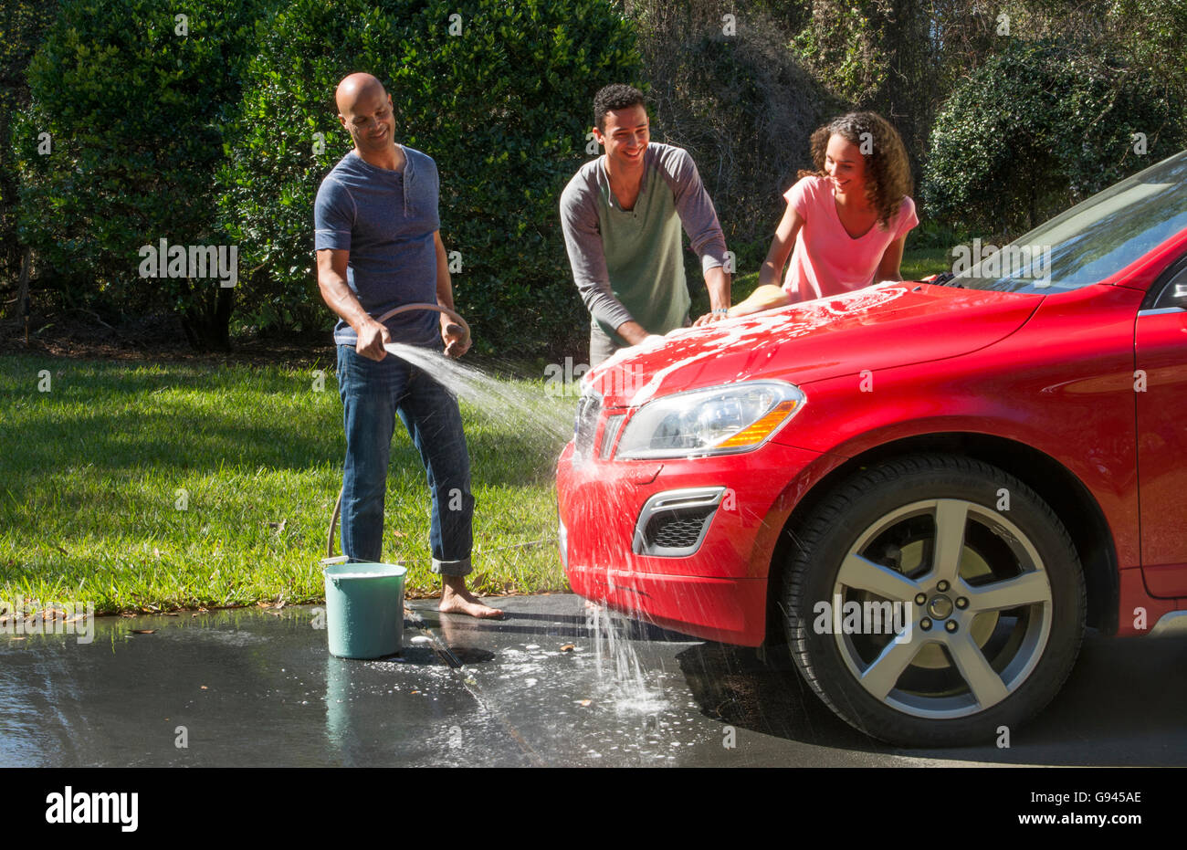 Family wash car at home black Caribbean dad son and daughter outside in sun red car fun together love Model Released, - Stock Image