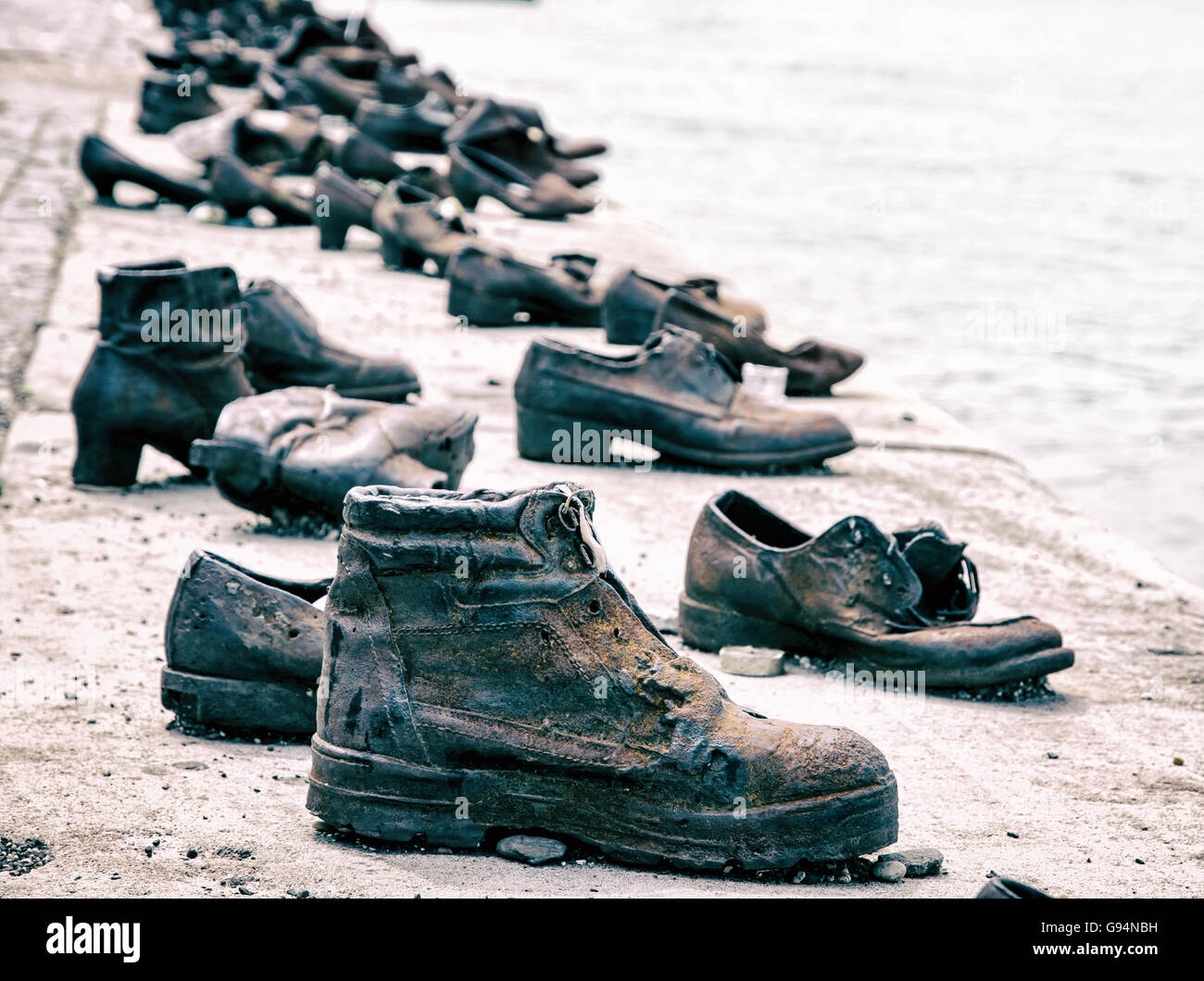 Shoes on the Danube bank is a memorial in Budapest, Hungary. Blue photo filter. Shoes monument. Place of reverence. - Stock Image