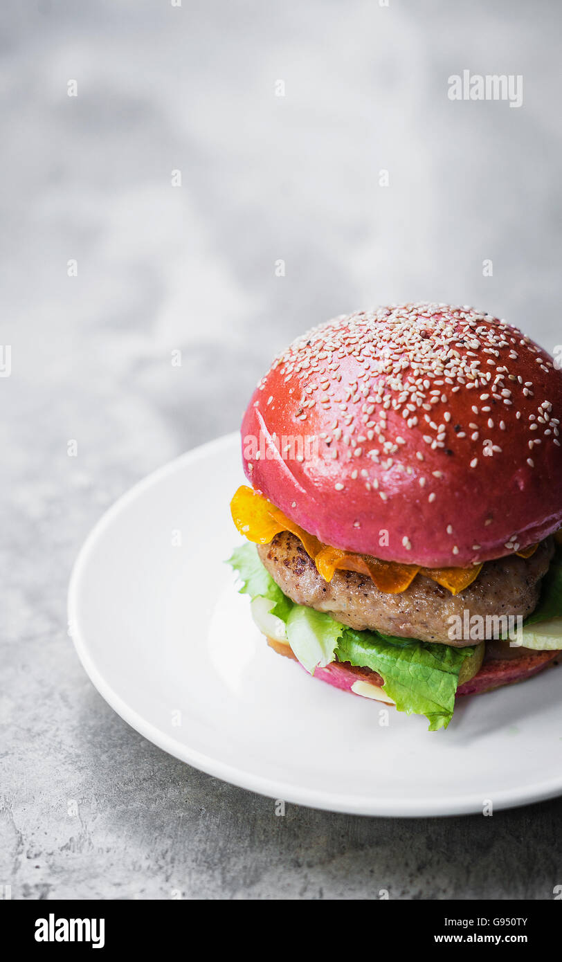 gourmet trendy modern novelty chicken burger in beetroot bun - Stock Image