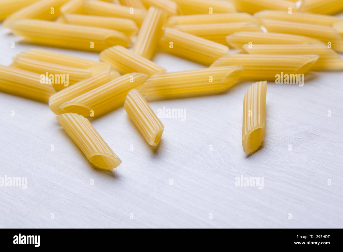 raw uncooked penne pasta on white table - Stock Image