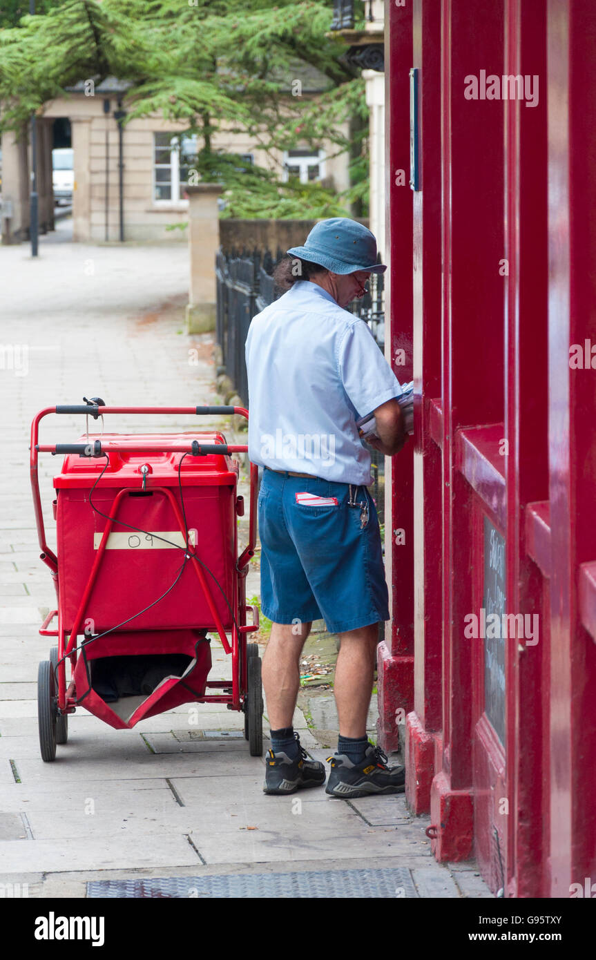 Postman makes a delivery in Bath, Somerset, England, UK - Stock Image