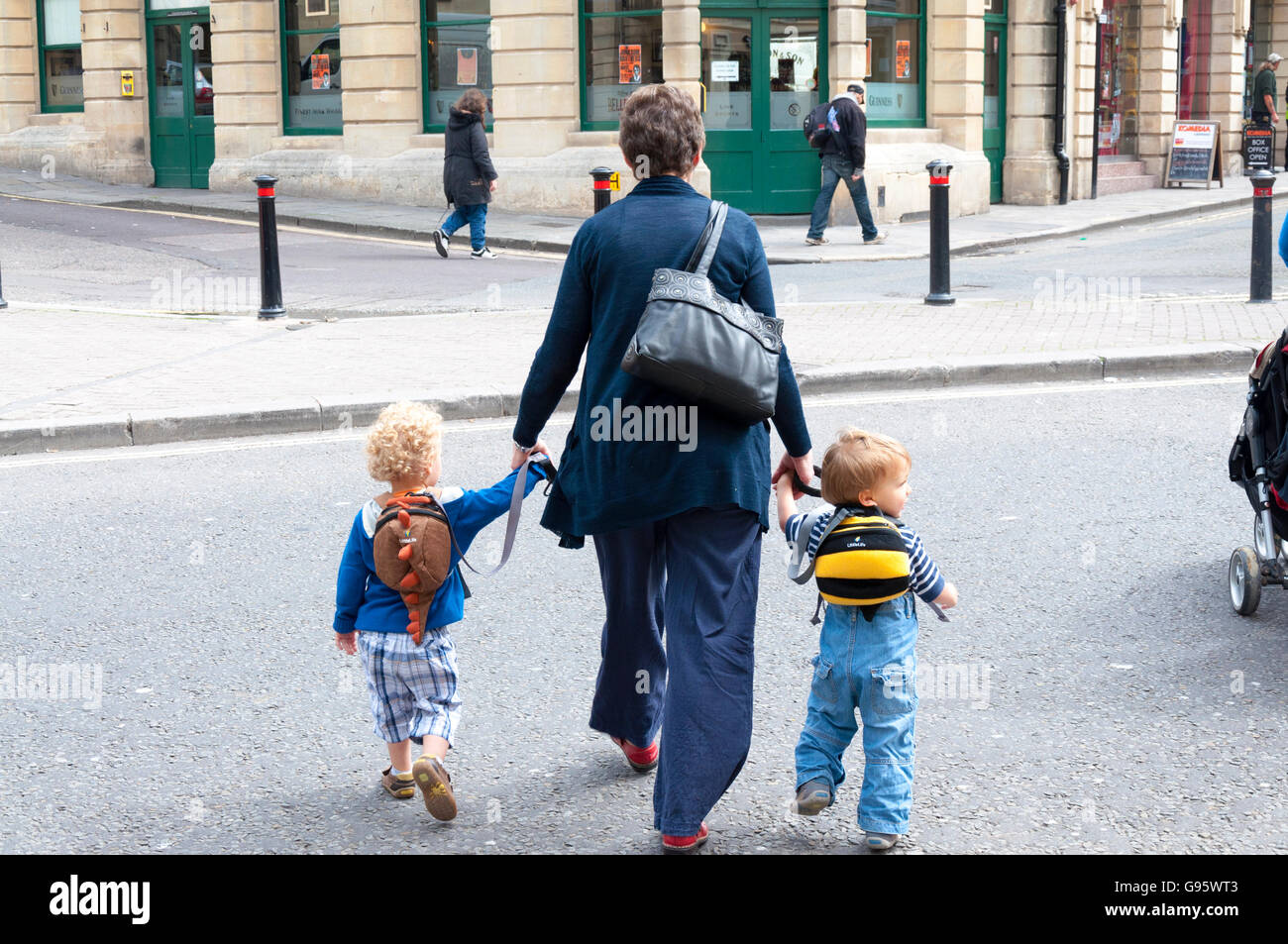 Crossing the road with young children in Bath, Somerset, England, UK - Stock Image