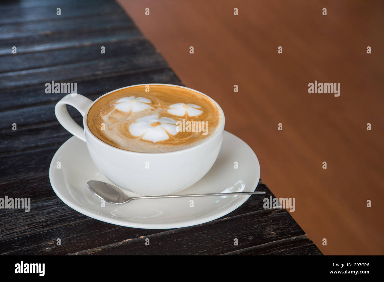 A cup of coffee with flower pattern in a white cup on wooden background. - Stock Image