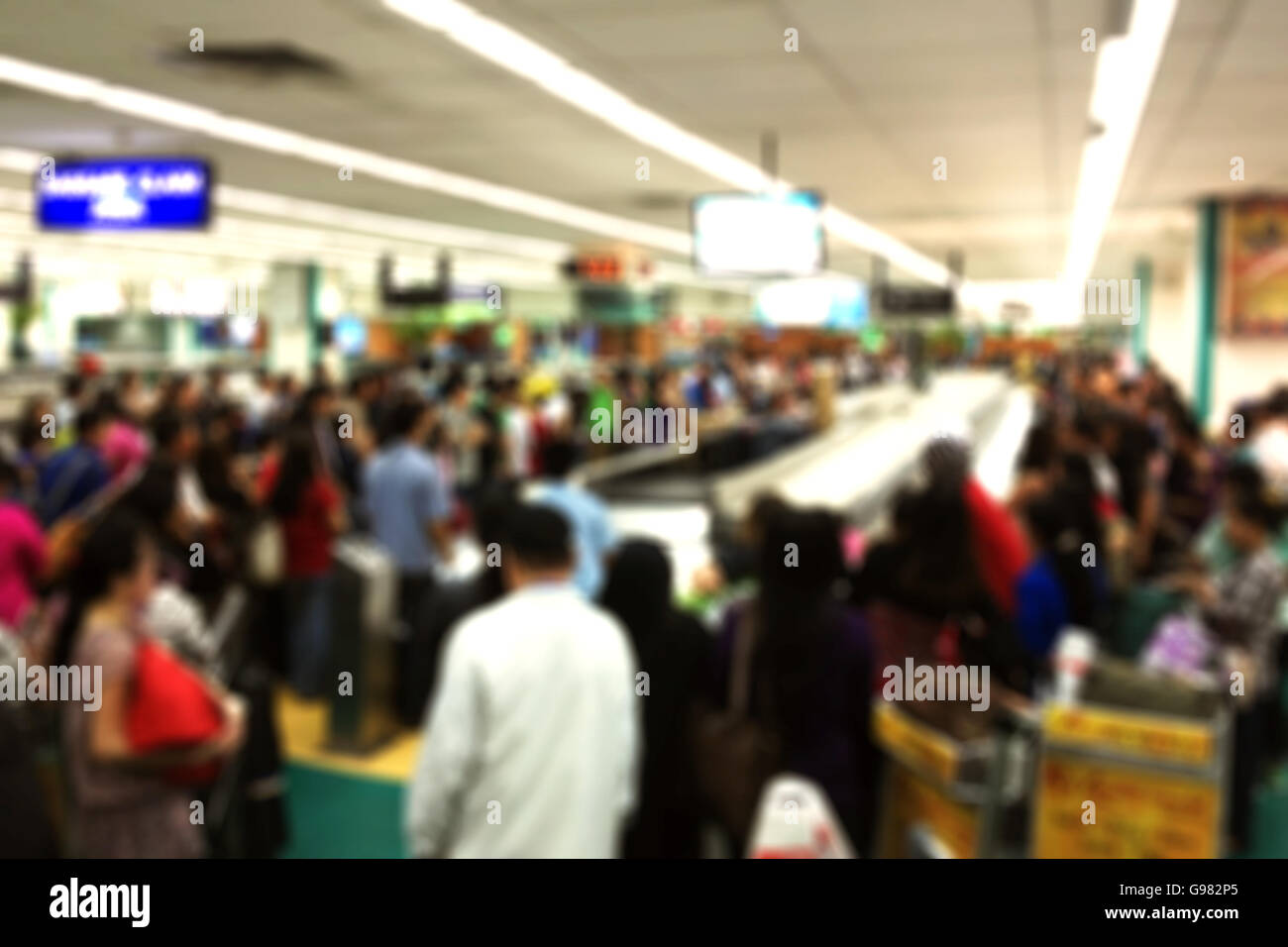 Blurred background of busy baggage claim area at an international airport - Stock Image