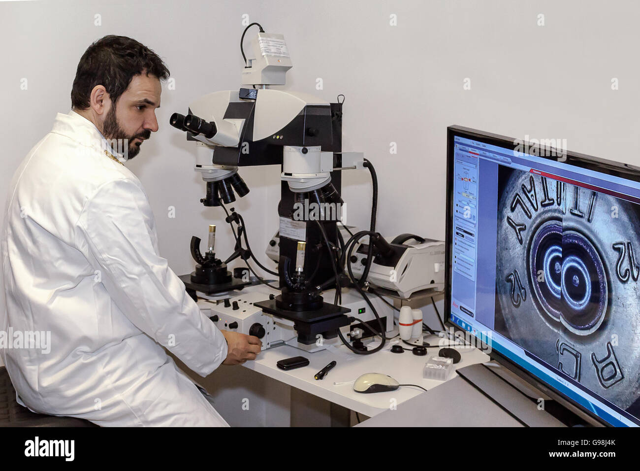 Rome, Italy - May 16, 2016: A police officer under the microscope the correspondence of two bullet casings to verify - Stock Image