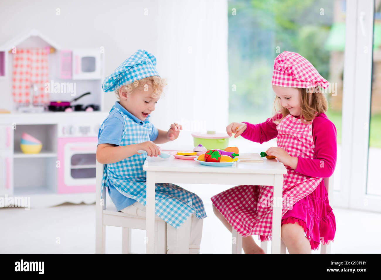 Little Girl And Boy In Chef Hat And Apron Cooking In Toy Kitchen.  Educational Toys For Young Children.