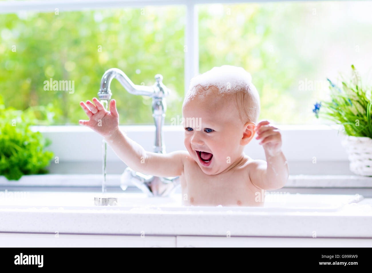 Baby taking bath in kitchen sink. Child playing with foam and soap ...
