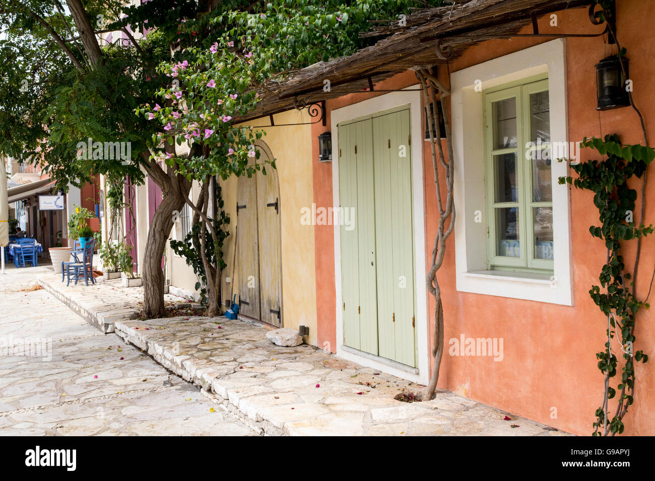 Shady Street View, Old Traditional Buildings and Terraced Paving with Flowers and Plants, Fiskardo, Kefalonia, Greece - Stock Image