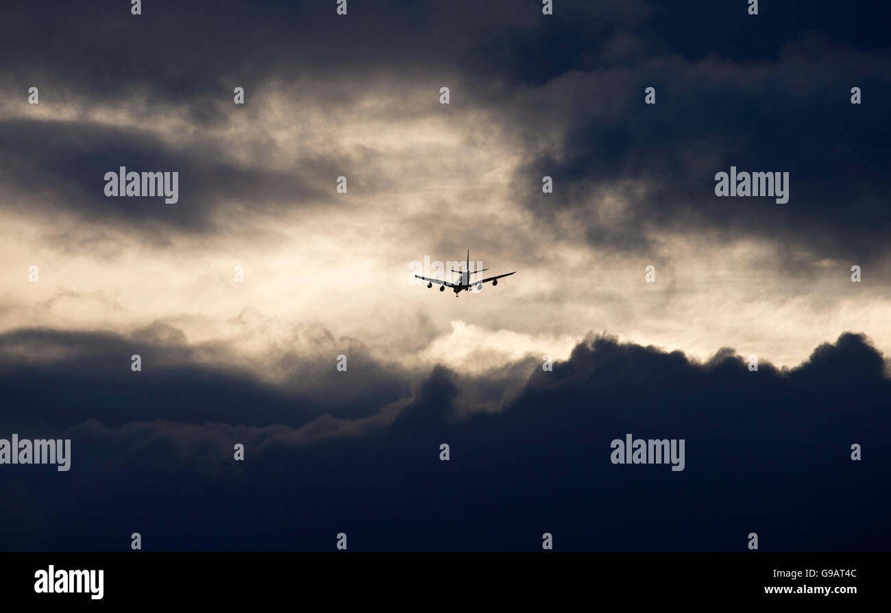 Aircraft flying into sunset at Heathrow airport - Stock Image