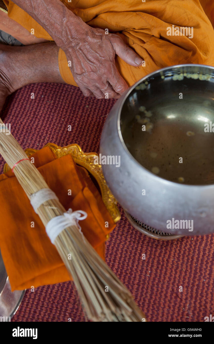 A monk squatting in a temple hall alongside a bowl of holy water and reed brush that are used in blessing ceremonies - Stock Image