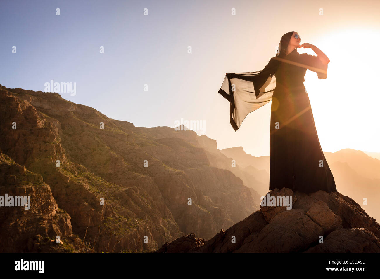 Lone woman in abaya in Al Hajar Mountains of Oman at sunset - Stock Image