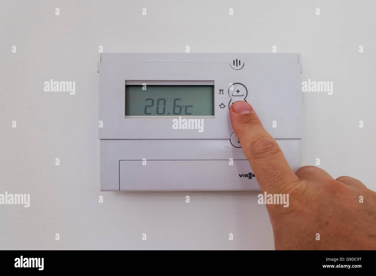 Man adjusting home central heating thermostat to lower temperature and save energy and money. - Stock Image