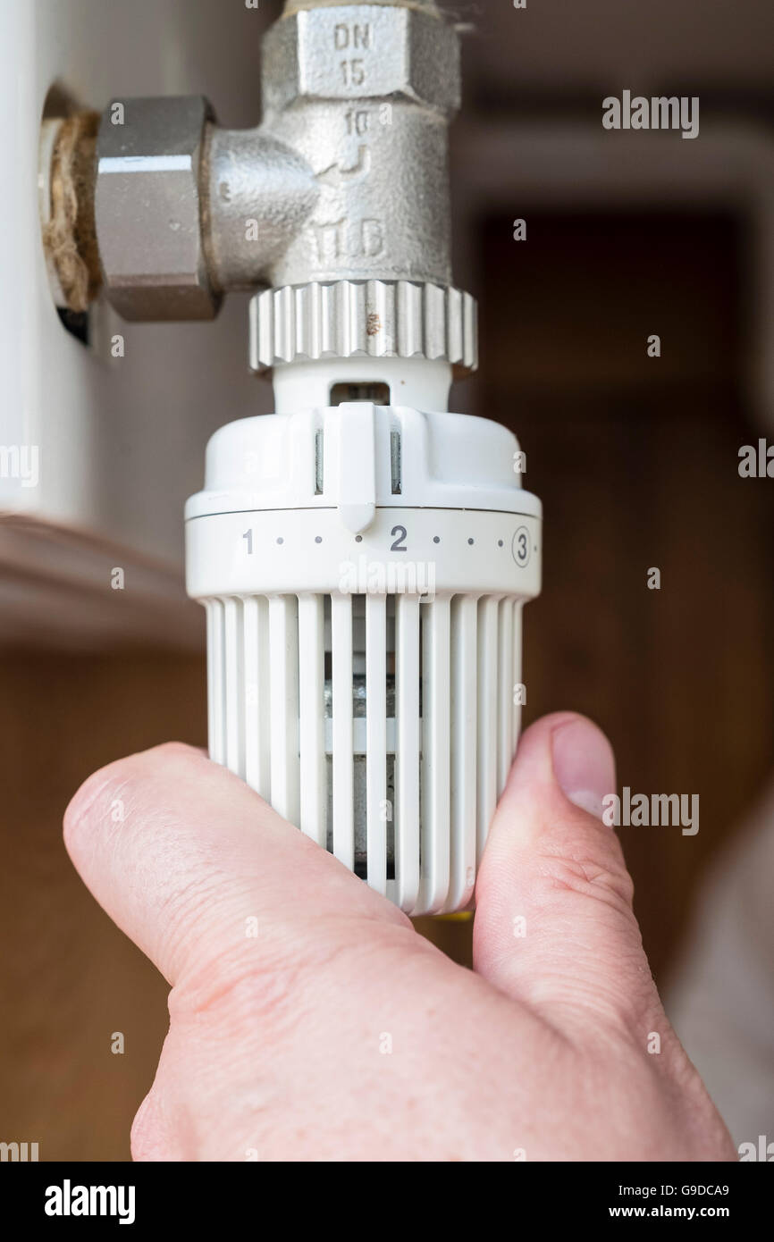 Man turning down thermostat on gas powered central heating radiator to save energy - Stock Image