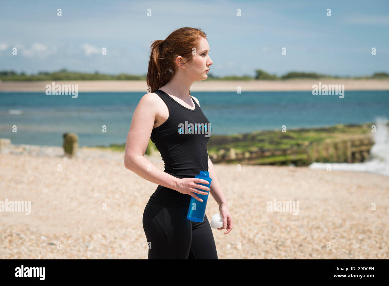woman wearing exercise clothing carrying a water bottle - Stock Image
