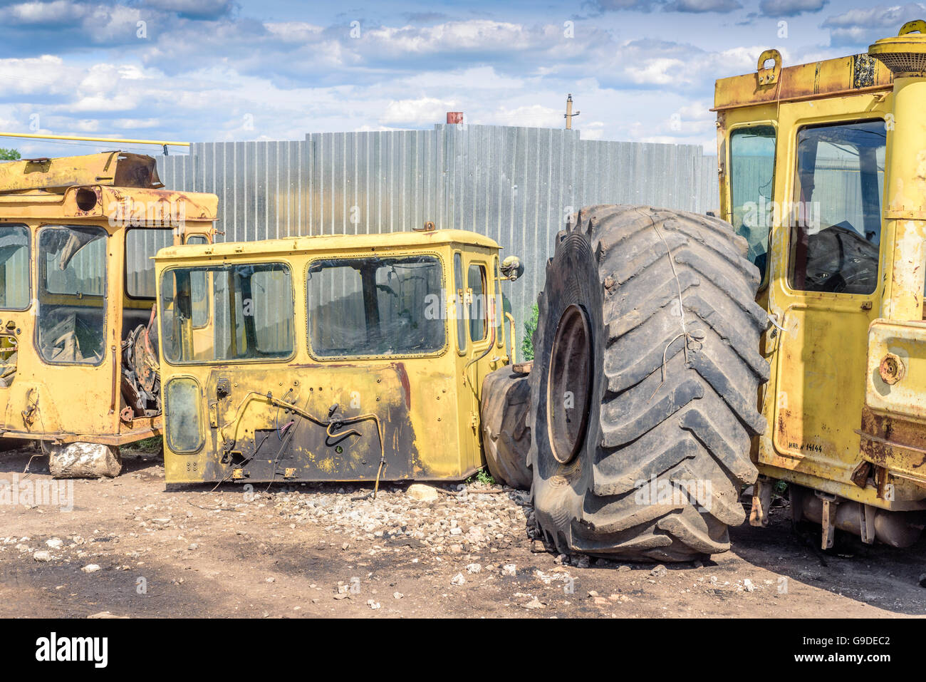 Broken and salvaged large yellow industrial machine cabins at a scrap breakers yard in non-working condition. - Stock Image