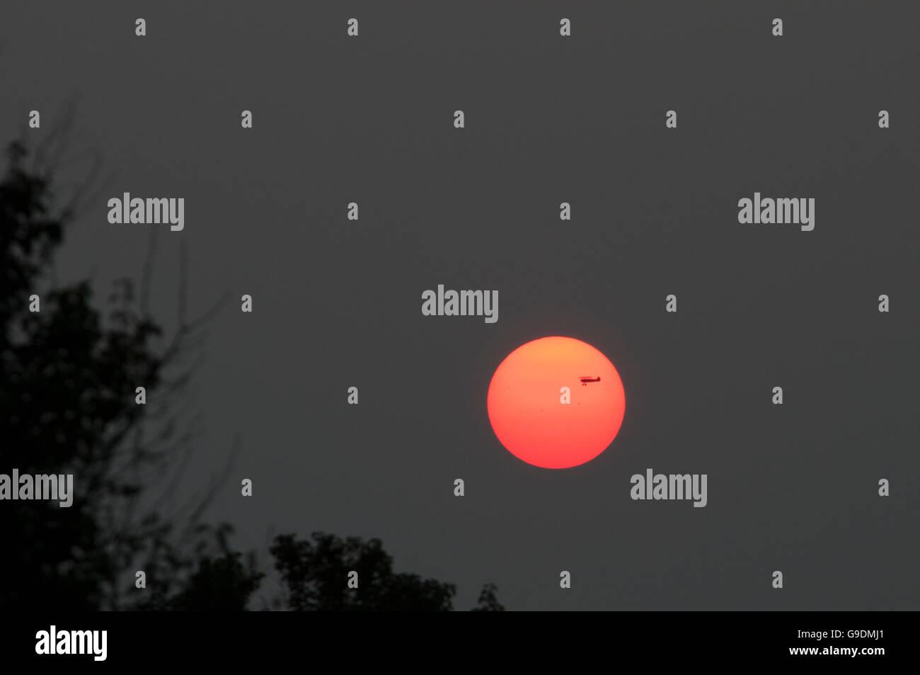 A bi-plane flies across the Indiana setting sun. - Stock Image