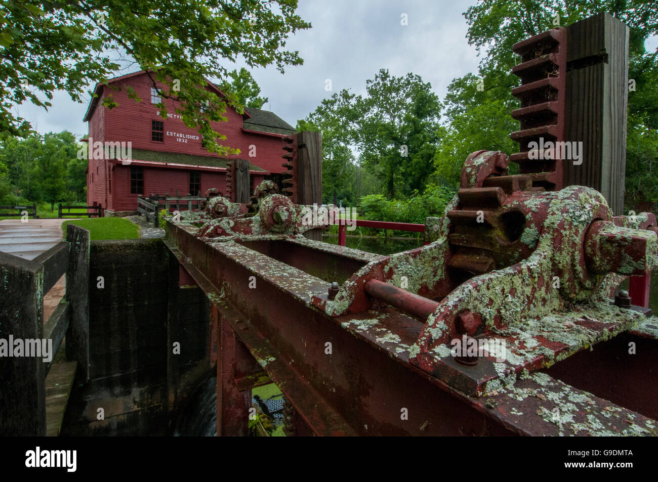 The gears and machinery to raise and lower water level at a grist mill. - Stock Image