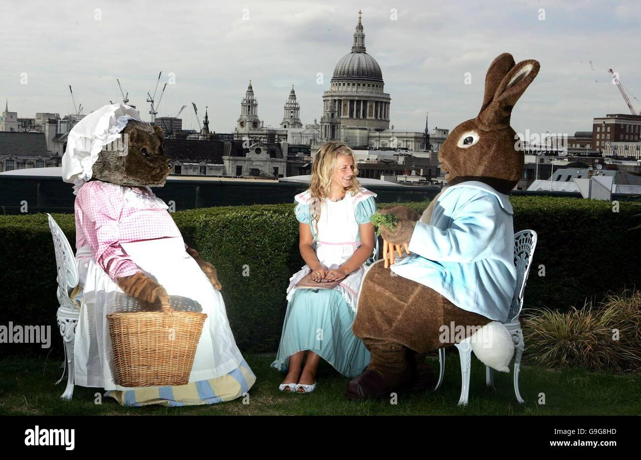 Sarah Rew (centre) as Alice joins Mrs Tiggywinkle (left) and Peter Rabbit (right) on a roof garden overlooking St - Stock Image