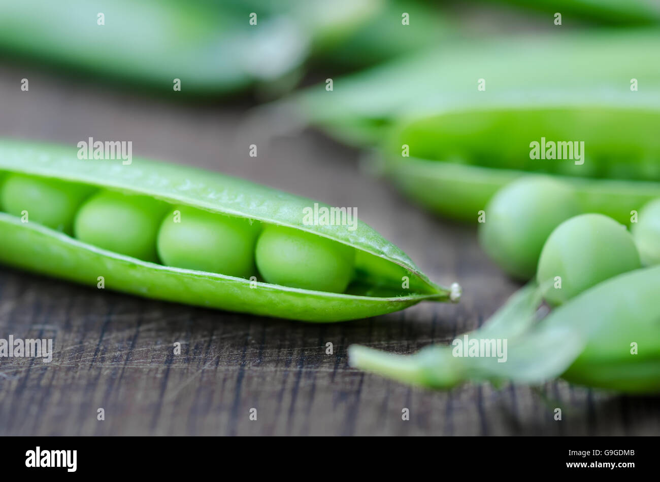 Organic peas pods on wooden table, rustic style - Stock Image
