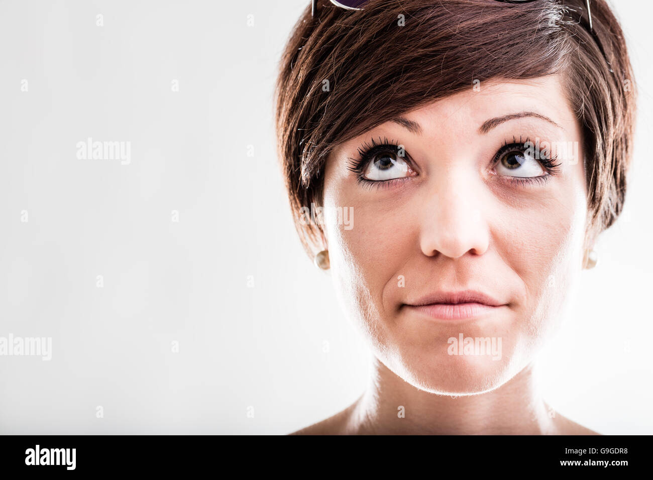 Thoughtful attractive woman looking up into the air with a serious pensive expression, close up head shot on white - Stock Image