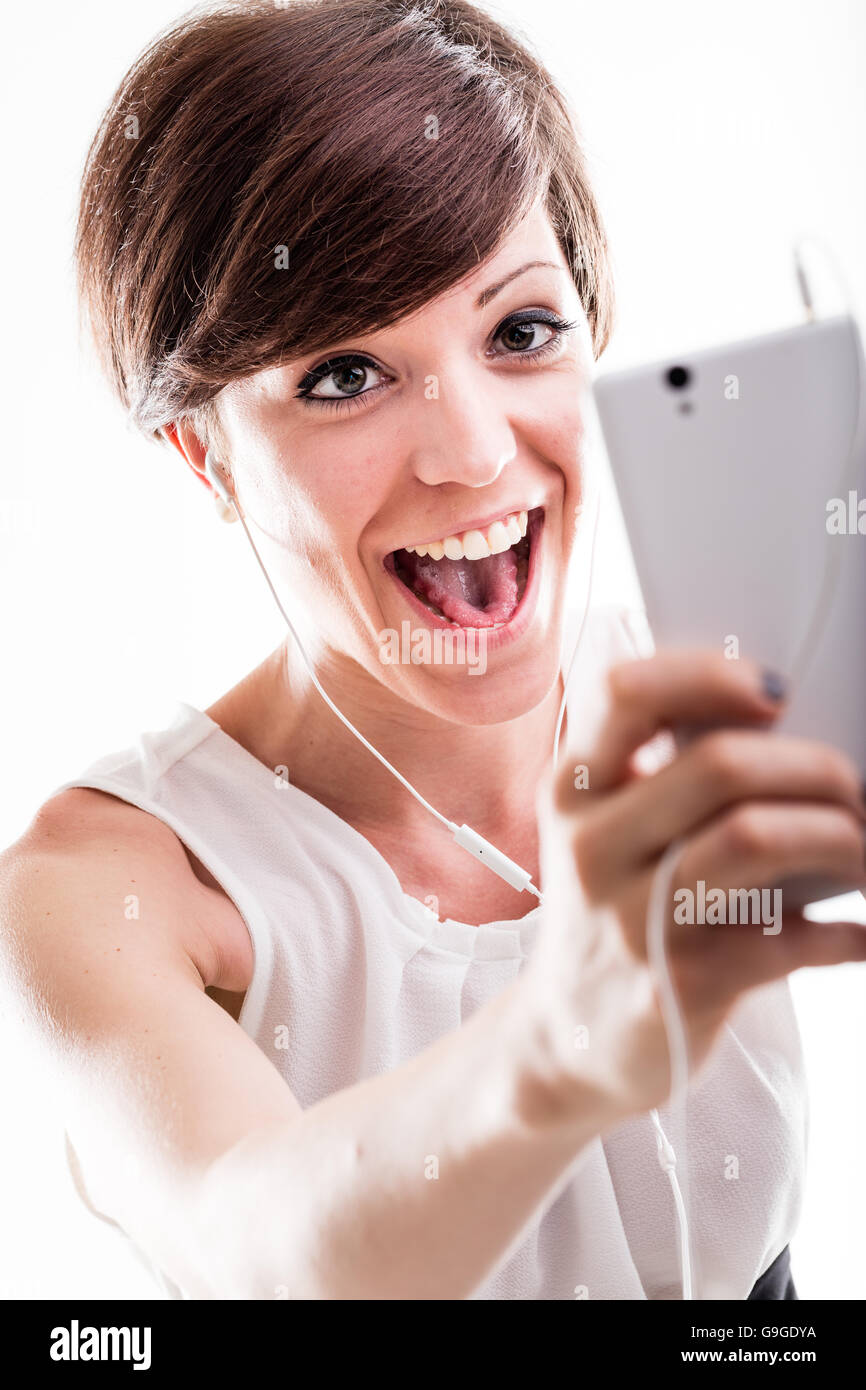 Laughing attractive woman posing for a selfie on her mobile phone with her mouth open and a happy expression - Stock Image