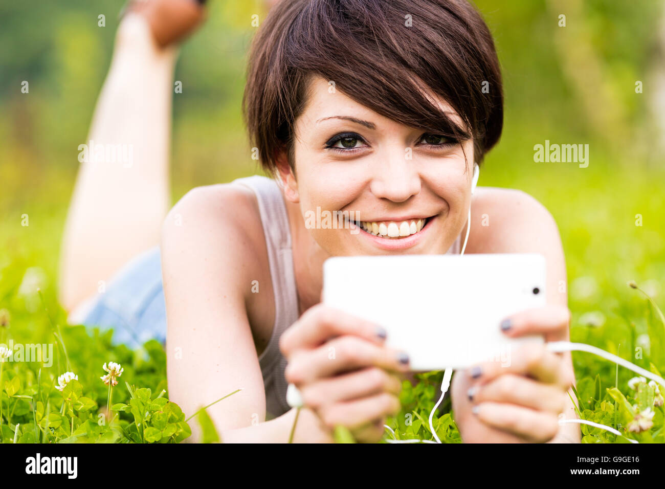 Smiling happy woman listening to music outdoors lying on her stomach on the grass holding her mobile phone, close - Stock Image