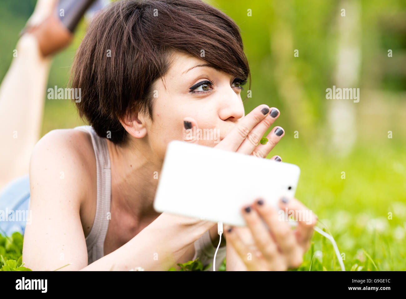 Young woman relaxing outdoors listening to music as she lies on her stomach in a lush green spring meadow holding - Stock Image