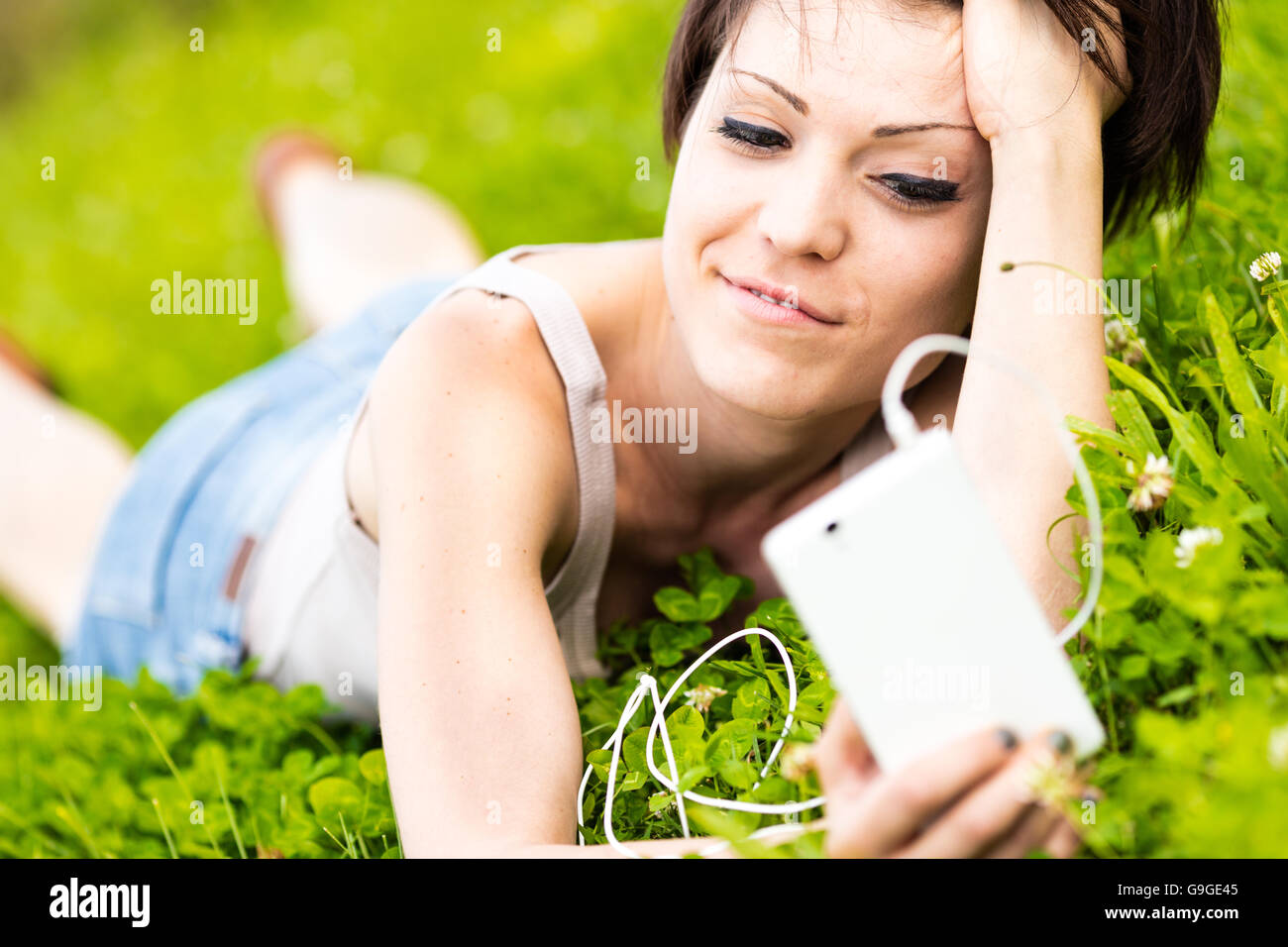 Attractive young woman relaxing in a meadow with her mobile phone and ear plugs reading the screen as she selects - Stock Image