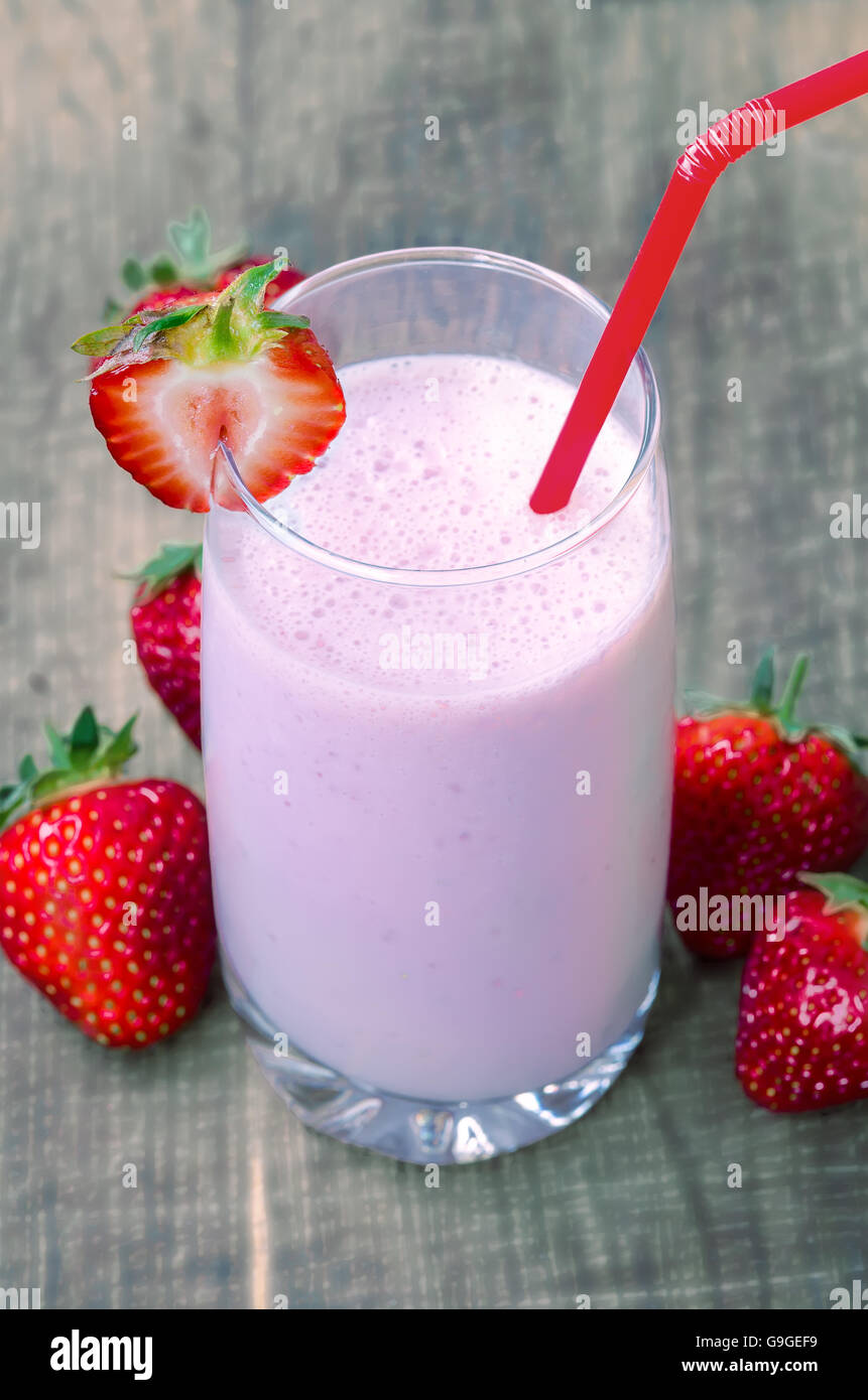 Strawberry milk shake with strawberries on wooden background, soft focus on strawberry on the glass - Stock Image